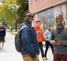 Students smile while walking on campus.